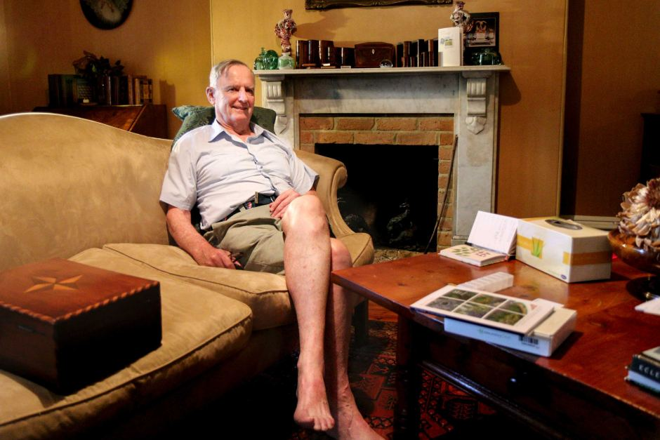 James Guest, wearing shorts and a shirt, sits on a plush couch with a fireplace in the background of an ornate sitting room.