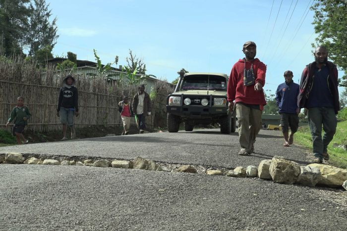 Locals fill a large crack in road with boulders in Mendi