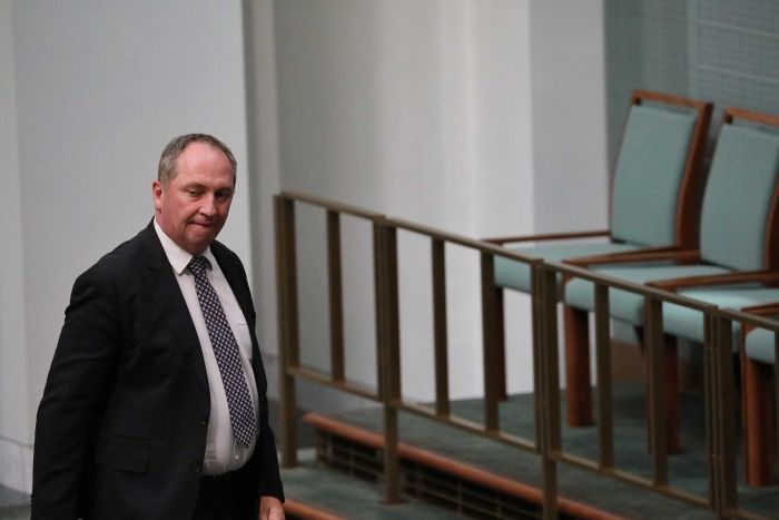 Barnaby Joyce, with an angry expression, walks past empty chairs