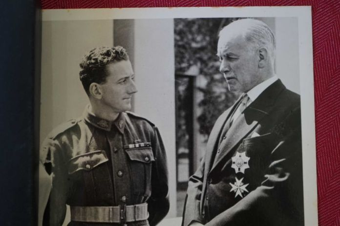 Old photo of man in medals meeting government official.