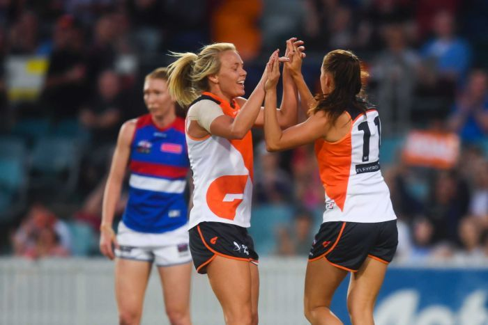 Aimee Schmidt of the Giants (R) celebrates her goal against Western Bulldogs at Manuka Oval.