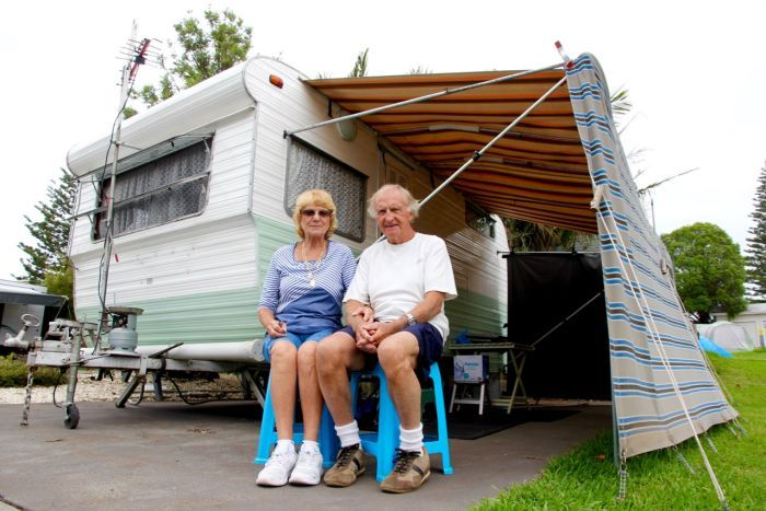 Two retirees, Ray and Annie Barrow, sit in front of their 1960s retro caravan