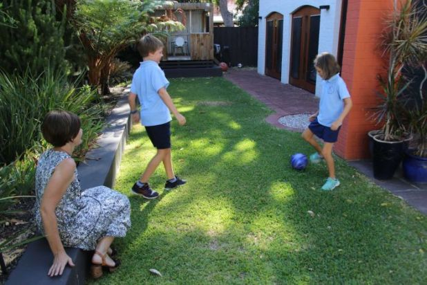 The two children kick a ball as their mother watches on.