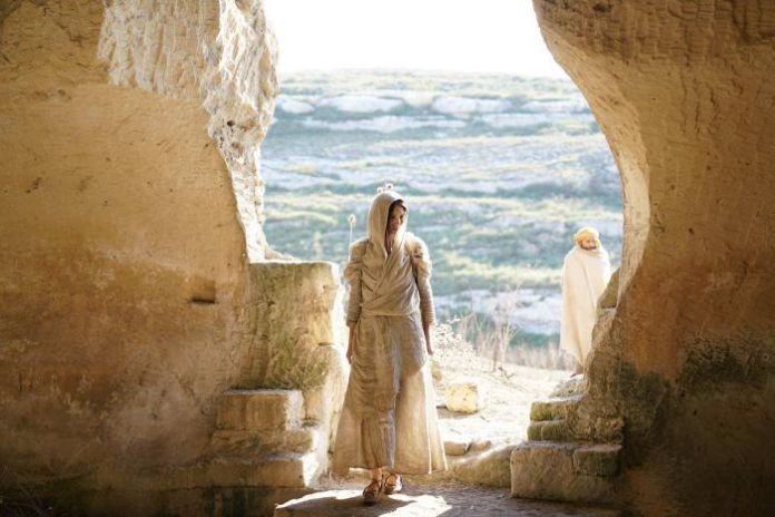 Colour still image from 2018 film Mary Magdalene entering a cave on a sunny day, wrapped head to toe in cloth.