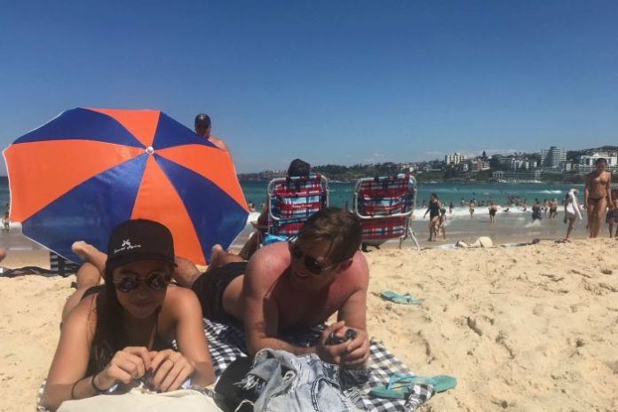 A man and woman lying on the sand try to keep cool at Bondi Beach in Sydney