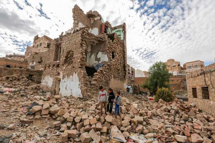 Three boys walk among the rubble of a bombed building in Sana'a, Yemen