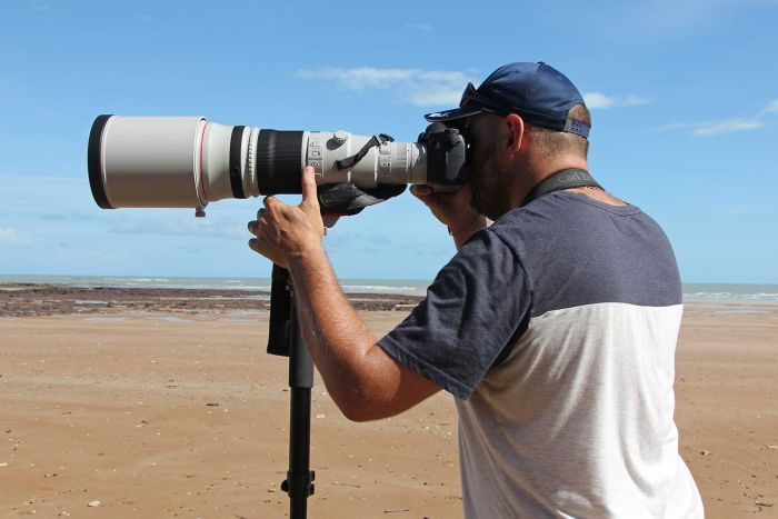 Birdwatcher Marc Gardiner looking into a long camera lens pointed out to sea.