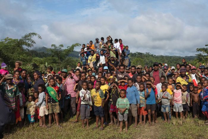 Wide shot of a large group of people standing in a clearing.