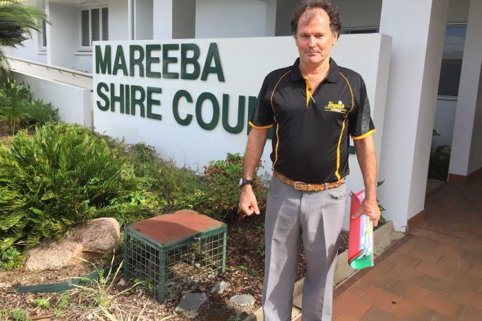 Man stands beside sign for Mareeba Council