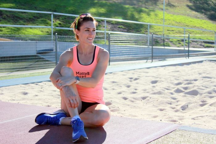 Athlete Lauren wells sits in front of the long jump sand pit.