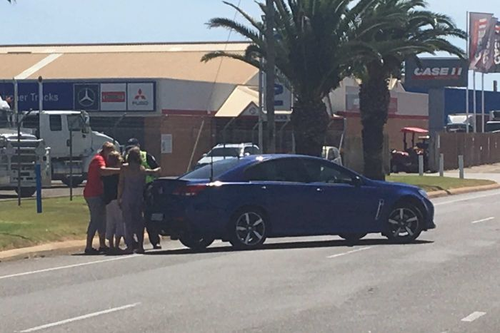 People on  the corner of Boyd Street and Flores Road in Geraldton near a blue car.