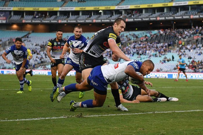 Moses Mbye of the Bulldogs barges through a tackle to score against Penrith at the Olympic stadium.