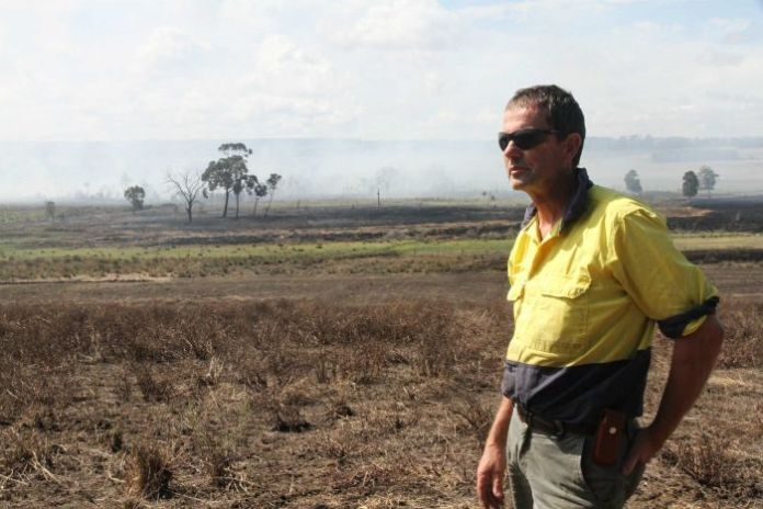A farmer looks out at a peat swamp burning on his property.