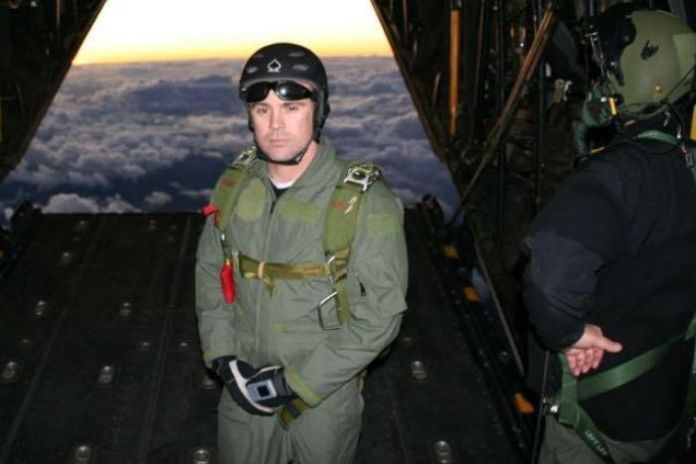 Tony standing near the open cavity of a plane above the clouds.