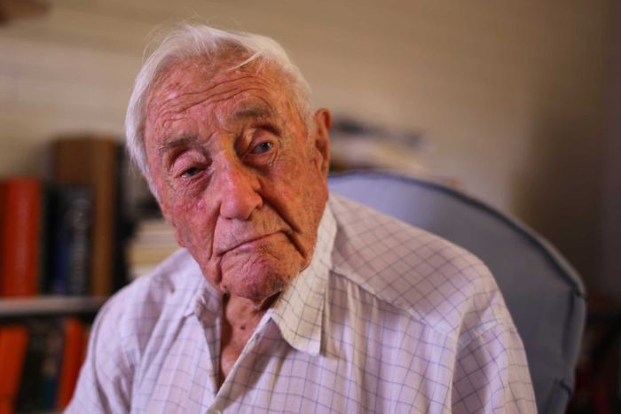 An elderly man sits on a chair in his home with a distant expression.