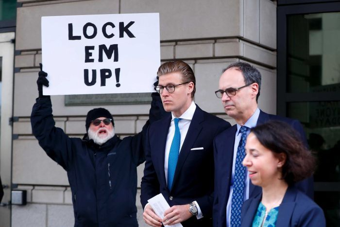 Alex van der Zwaan leaves court. A man standing near the entrance holds a sign that reads 'lock them up!'