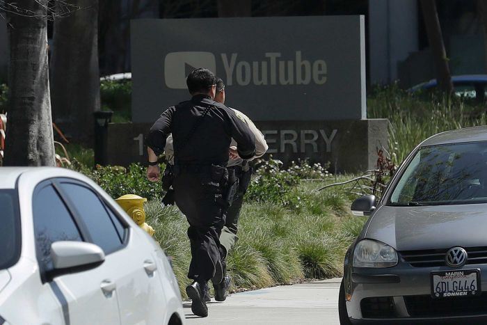 Officers run toward a YouTube office in San Bruno.