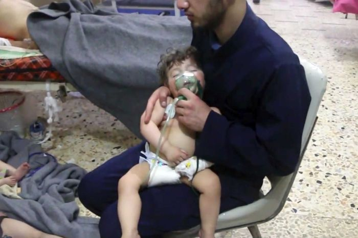 A medical worker gives a toddler oxygen. Someone is laying in a bed beside him. There are patients on the floor, one is a child.