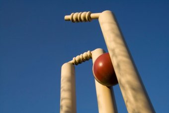 A red cricket ball breaks the wickets.