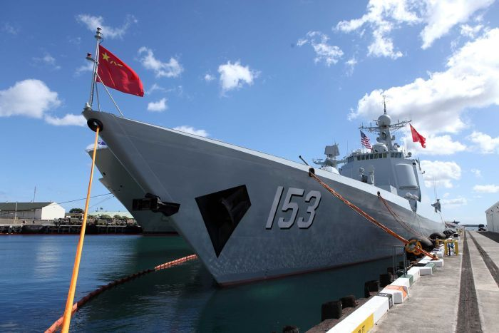 A Chinese Navy destroyer, with the Chinese flag waving at the front, can be seen tied to a dock.
