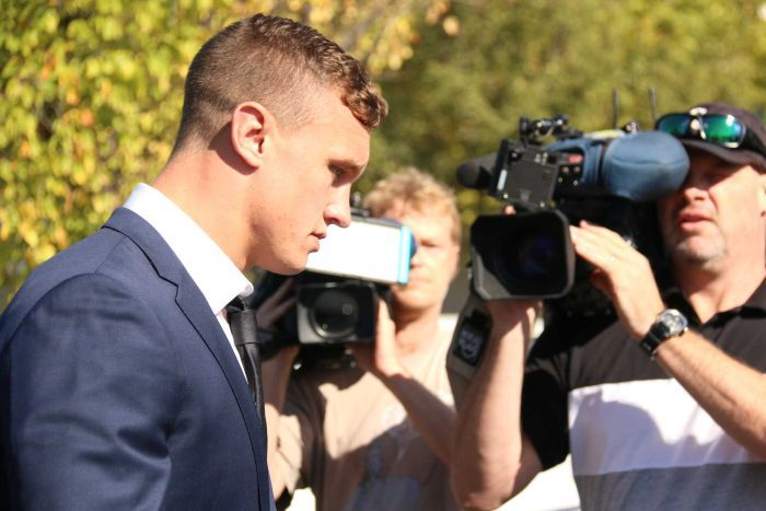 Jack Wighton, in a suit, walks with his head down while cameramen record him.