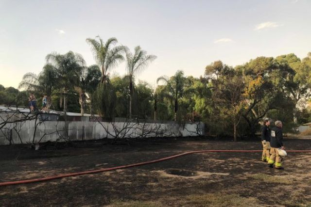 Firefighters stand on burned ground in Parafield Gardens