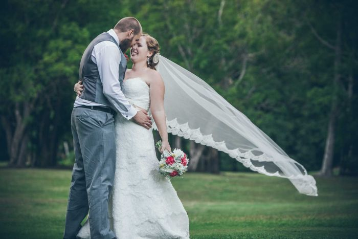 A bride and groom in a park share a hug with their heads touching together