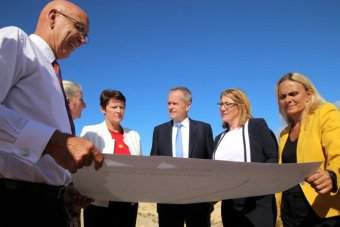 Labor Leader Bill Shorten in suit and blue tie, with several WA Labor Party people, inspect a map.