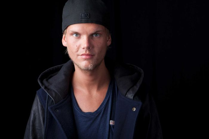Avicci stands in front of a black background.