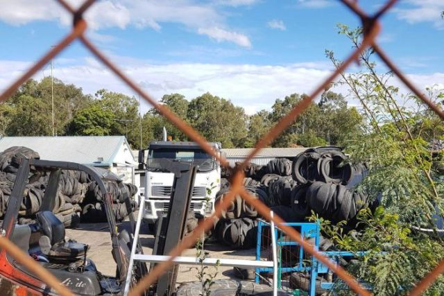 Piles of tyres and a truck behind a rusty cyclone wire fence