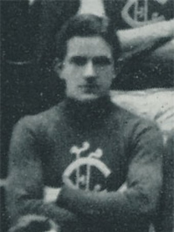 A black and white photo of a footballer with his arms crossed.