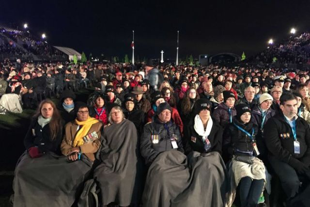 Crowds sitting in the early morning at Villers-Bretonneux in France for Anzac Day