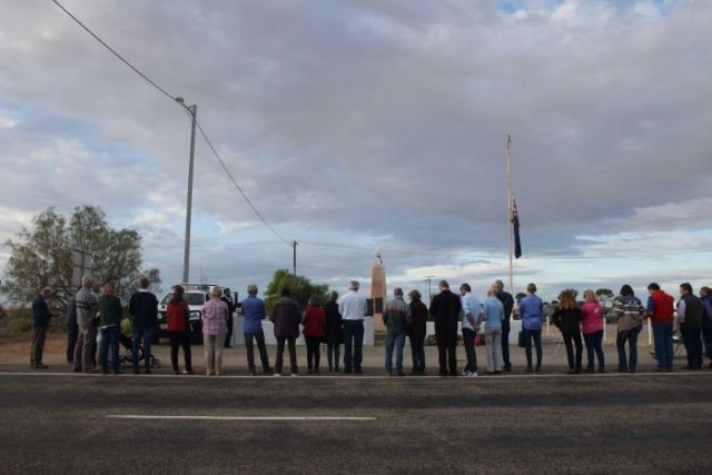 A line of people stands in front of a war memorial.