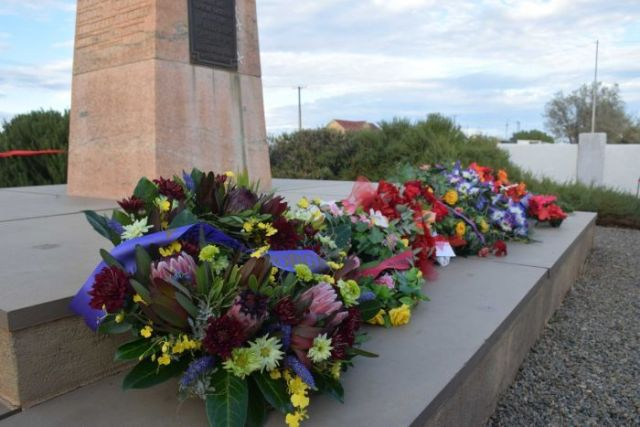 Floral wreathes laid at the base of a war memorial.