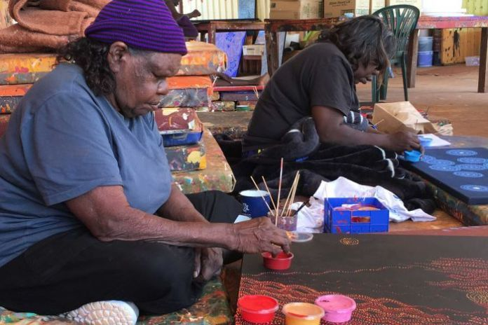 Two Indigenous artists hold paint brushes in their hands as they paint a canvas on the ground.