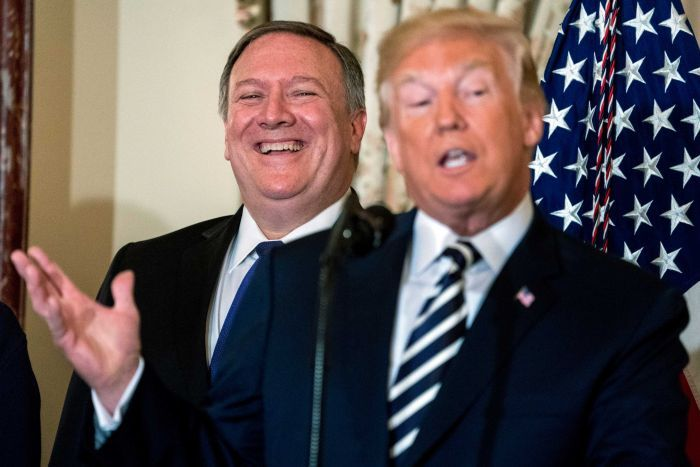 Mike Pompeo wears a big grin on his face as he stands behind Donald Trump, gesturing with his right hand, mid-speech