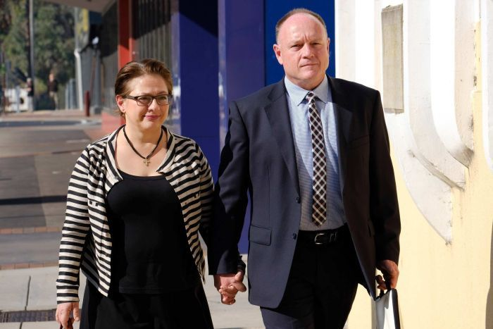 Sophie Mirabella walking down the street to court holding her husband's hand.