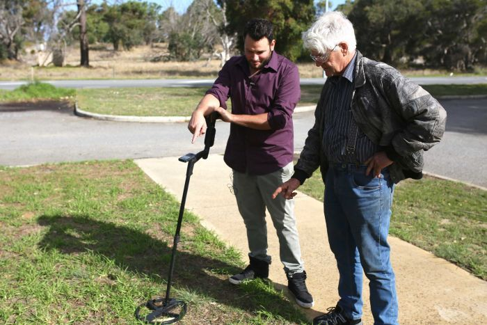 Two men with a metal detector on a patch of grass.