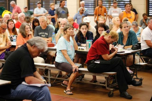 Evacuated residents hold a prayer before the start of a community meeting.