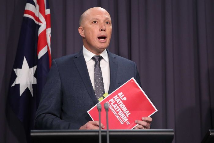 Home Affairs Minister Peter Dutton holds a Labor party document while talking to the media