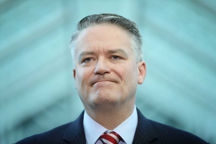 Tight shot of Cormann, lips held together, looking straight ahead.