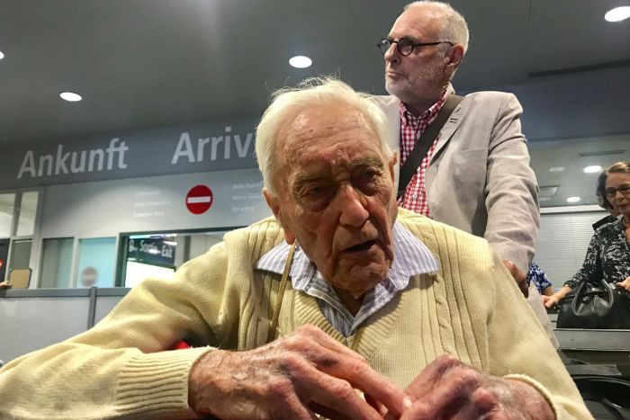 An elderly man in a tan jumper sits on a wheelchair being pushed through an airport by a man in a white coat and black glasses.