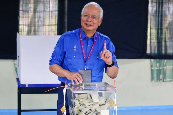 Malaysian Prime Minister Najib Razak smiles at a polling booth.