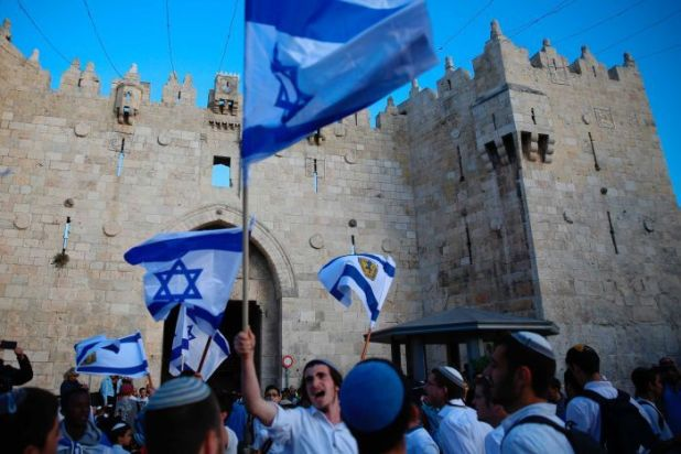 Israelis wave national flags outside the Old City's Damascus Gate.