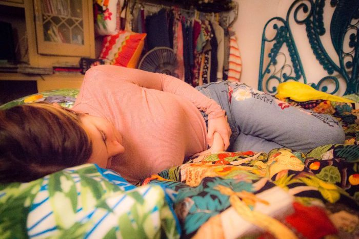Kit Richards lies on her bed holding her abdomen.