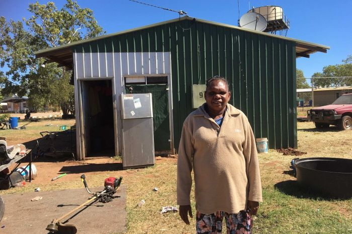 Samantha Campbell stands in front of a tin shed house.