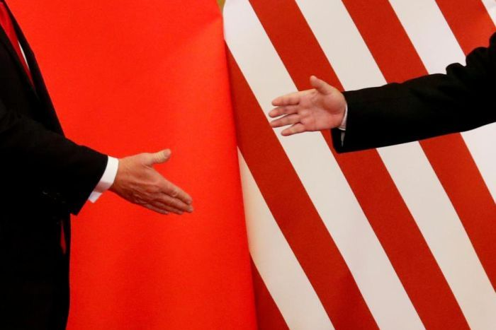 US President Donald Trump and China's President Xi Jinping about to shake hands.