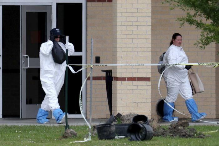 Officials retrieve belongings from inside the school which remains closed.