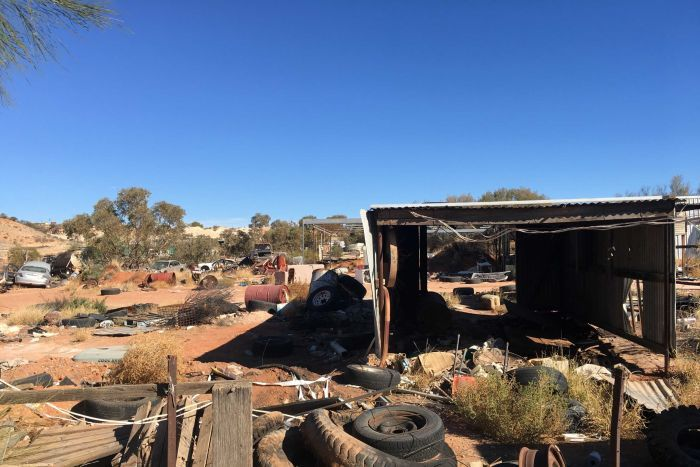 Rusted cars, old tyres, oil barrels and a derelict shed sit on a dusty red desert landscape