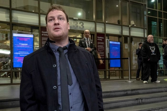 Ricky Turner, dressed in a blue shirt and black tie and jacket, stands outside Melbourne Magistrates' Court.